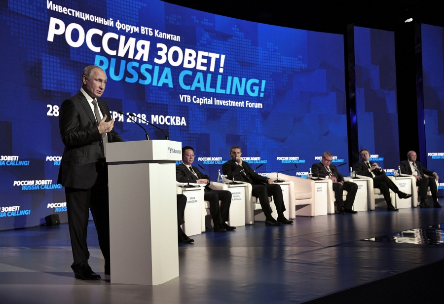 Russian President Vladimir Putin stands at a podium. To his right are other officials seated on a stage.