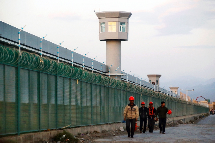 Men in orange hard hats walk alongside a large fence topped with barbed wire. Behind the fence are lookout towers.