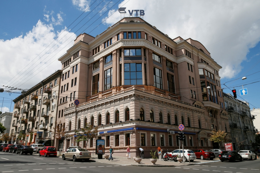 A older brick building is on the corner of a street. Atop the building is the logo for VTB bank.