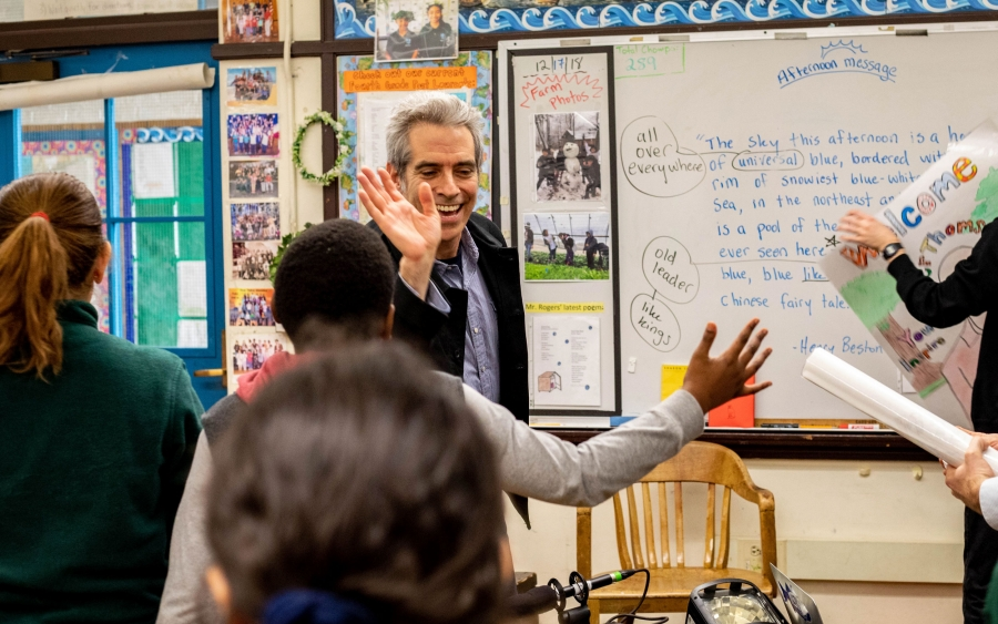 A man high fives a child in a school classroom.
