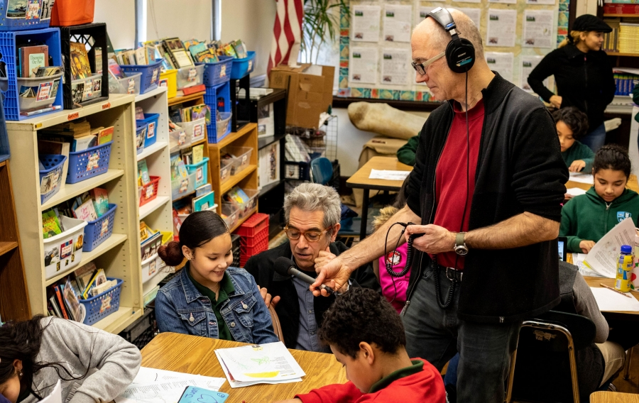 A young girl sits at a school table and reads while a man holds a microphone next to her and records her reading.