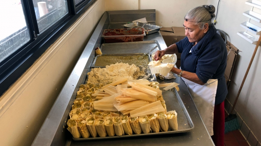 A woman stands a at a table assembling tamales
