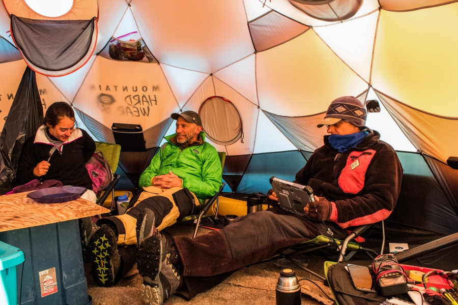 The crew gathered is shown lounging in chairs for meals in a tent on the ice.