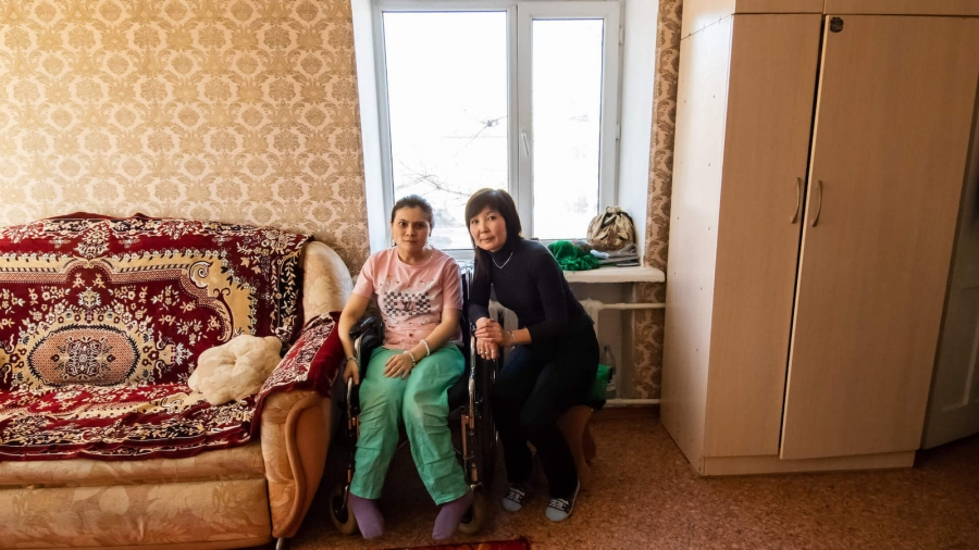 A young woman sits in a wheelchair next to her mom in the living room.