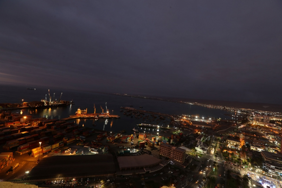 In this wide angle photo taken at dusk, Arica city is shown with shipping facilities on the water.