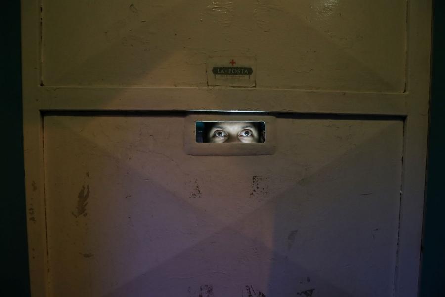 Venezuelan migrant Angel Torres is shown looking through a peep hole at La Posta restaurant.