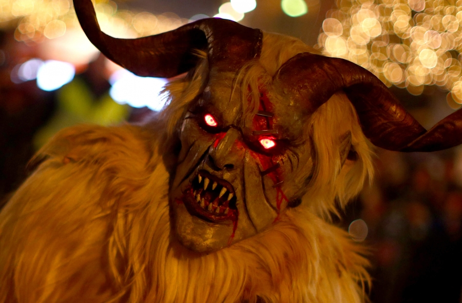 a closeup of a Krampus mask with glowing eyes