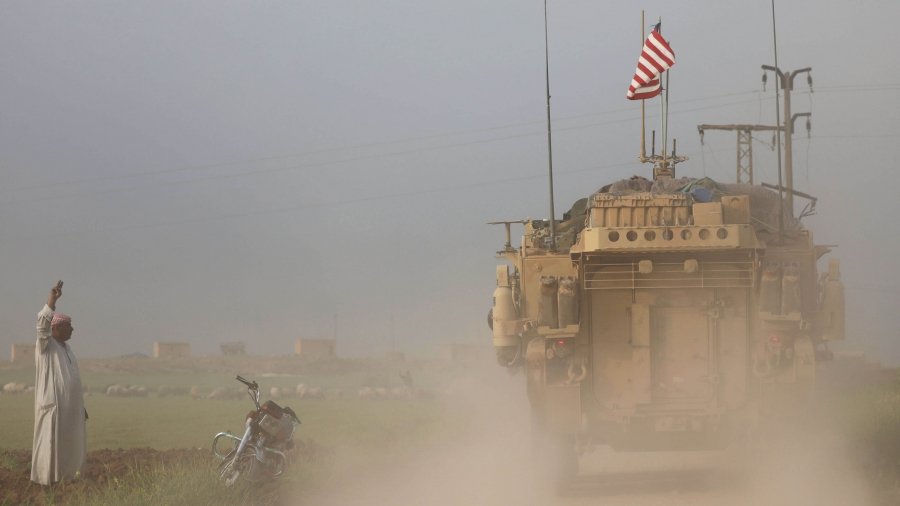 A man gestures at US military vehicles as dust colors the air