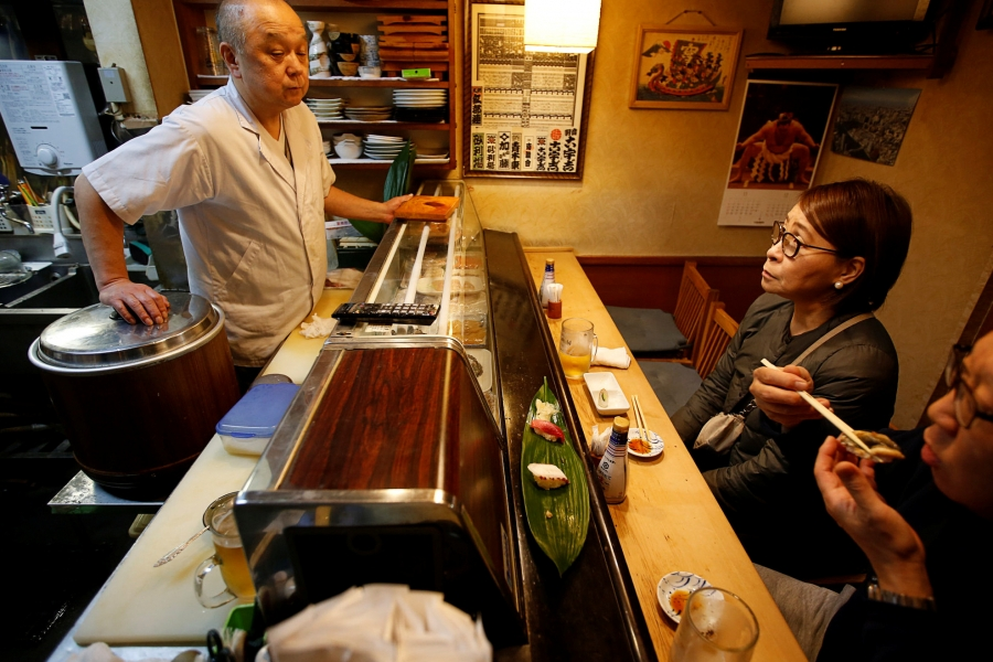 Chef chats with customers at sushi bar.