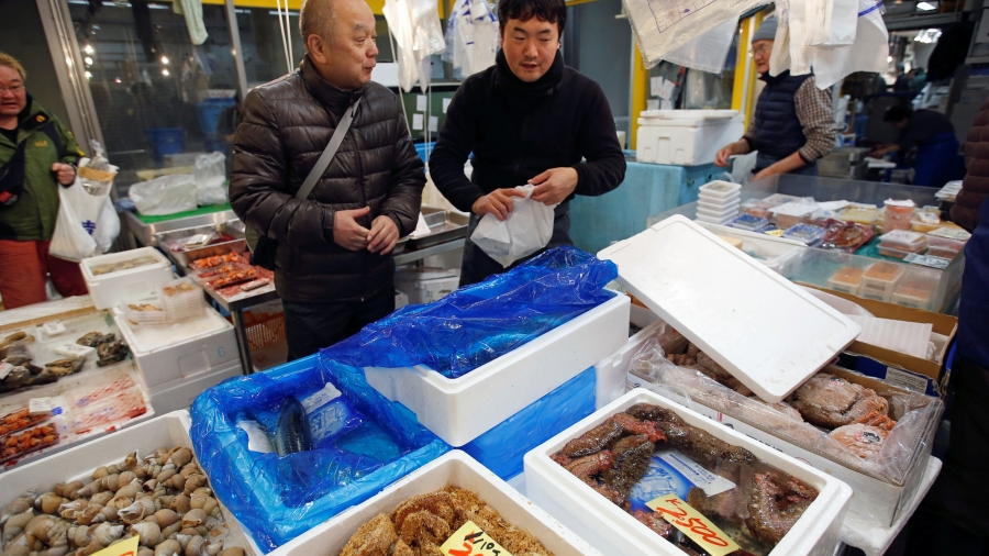 Two men stand near fish in bins at fish market.