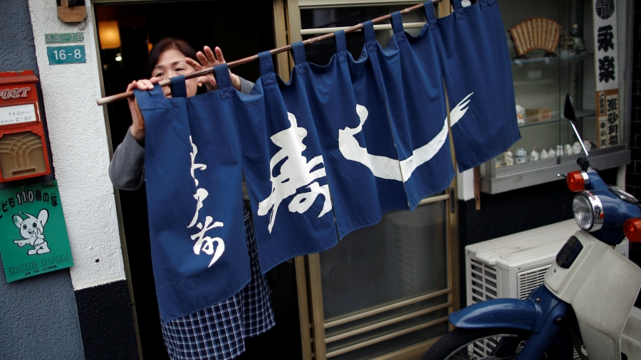 A woman moves a blue curtain with Japanese script as she opens the restaurant.
