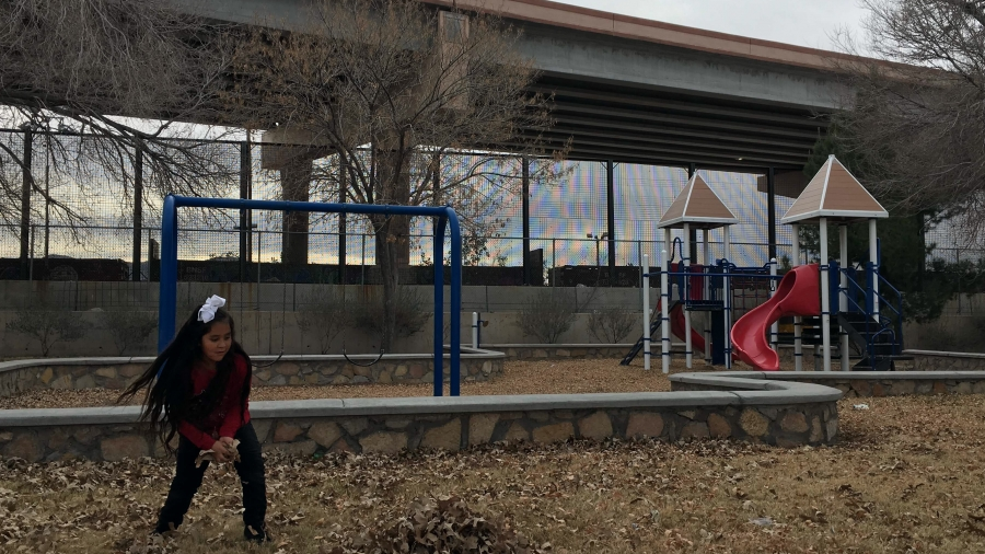 A little girl plays in a park with 18-foot steel border fence in backdrop.