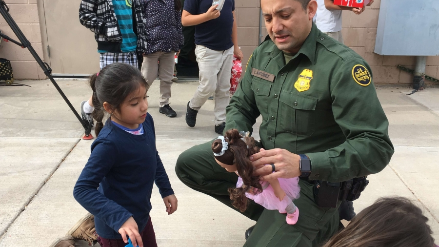 Border patrol agent helps a young girl dress a doll.
