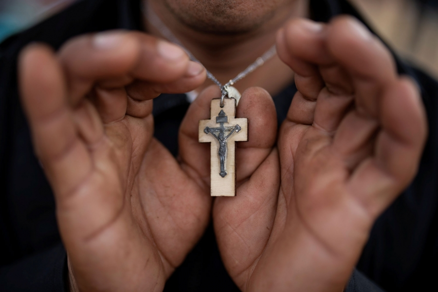 A close-up photography of Nicolas Alonso Sanchez holding his wooden cross.