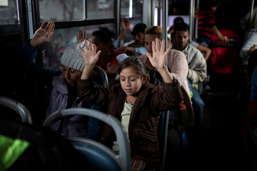 Migrants are shown with their hands raised in the air praying on a bus.