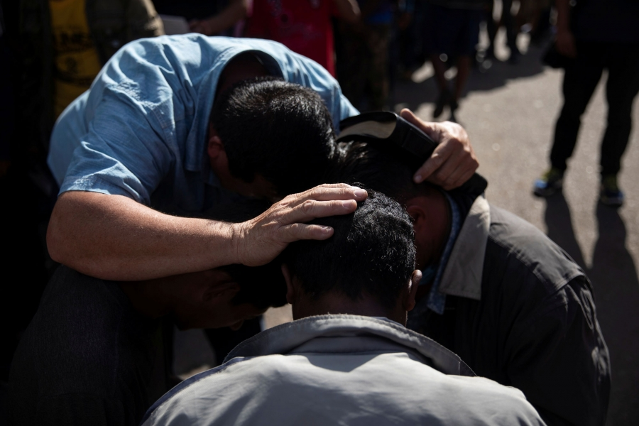 Pastor Jose Murcia is shown with his hands on two people's heads preaching.