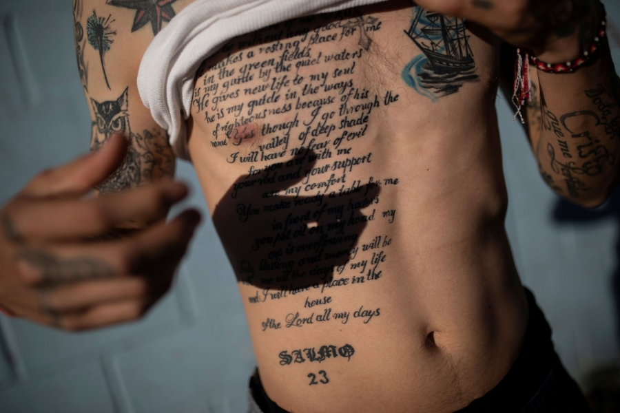 Juan Francisco is shown lifting his white shirt up to reveal a large tattoo of the 23rd Psalm of the Book of Psalms written out.