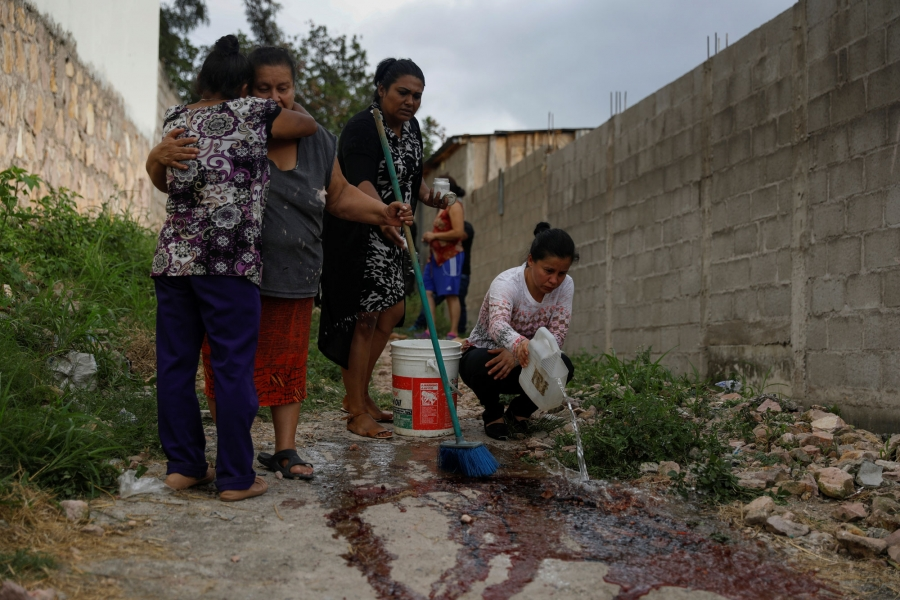 Relatives and friends of Ronald Blanco are shown in the street, a pair hugging and another wash the blood from the crime scene.