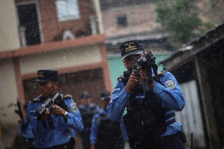 Several police officers are shown with high-powered riffles taking aim while on patrol .