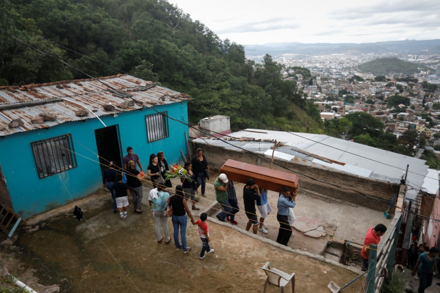Relatives and friends of Ronald Blanco are shown walking out of a blue house on a hill overlooking Tegucigalpa, carrying his coffin.