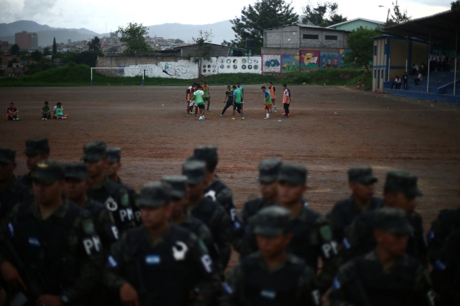 A group of people play soccer in the distance as soldiers are shown in the near ground lined up.