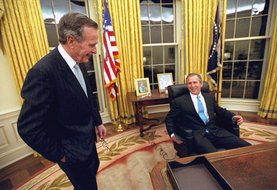 George W. Bush sits at the desk in the Oval Office while his father, H.W. Bush, stands off to the left.