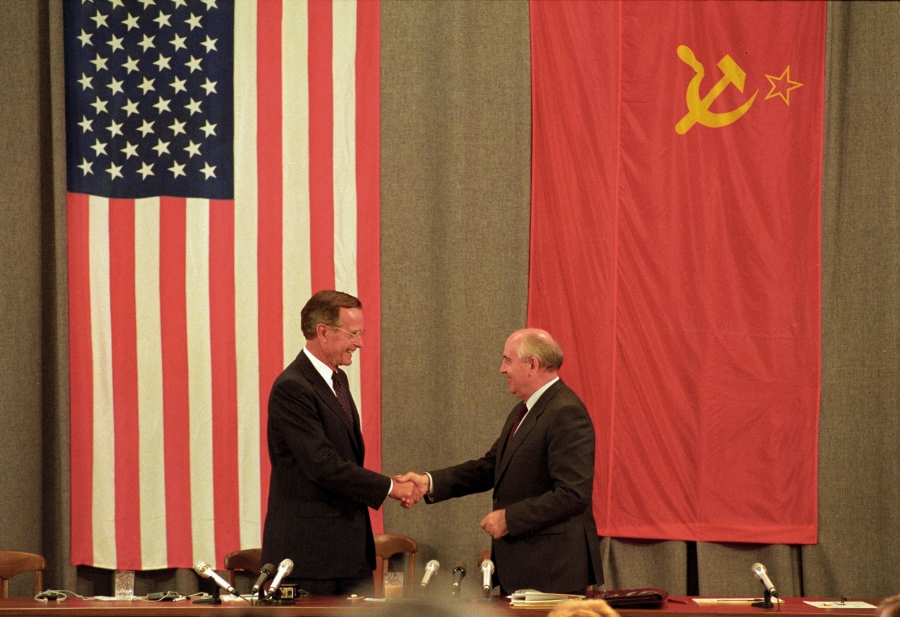 President HW Bush stands in front of an American flag and Soviet President Mikhail Gorbachev stands in front a Soviet flag as the two shake hands.