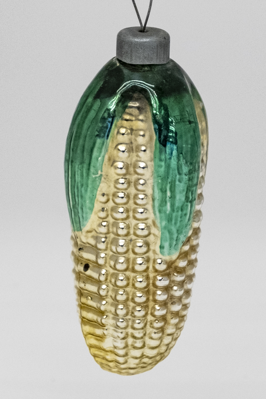 A golden tin corn-shaped ornament with green-painted leaves.