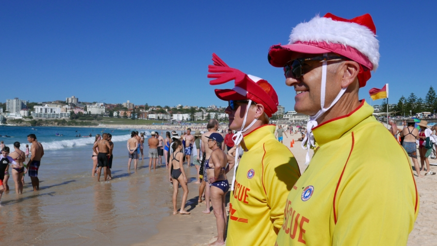 Two men wearing Santa Claus's hats stand on a sunny beach surrounded by people in bathing suits in Sidney Australia.