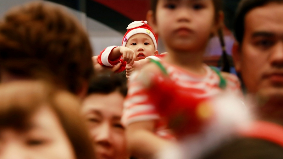 A toddler is dressed up as Santa Claus and looks at the camera while looking over a crowd of people.