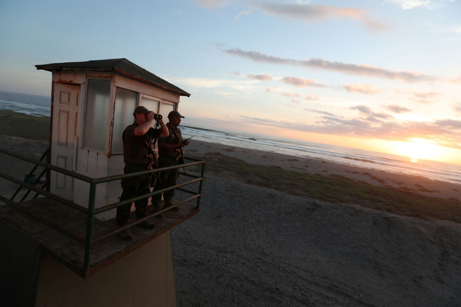 Two policemen look out from a watchtower — one looking through binoculars — at the Chilean and Peruvian border.