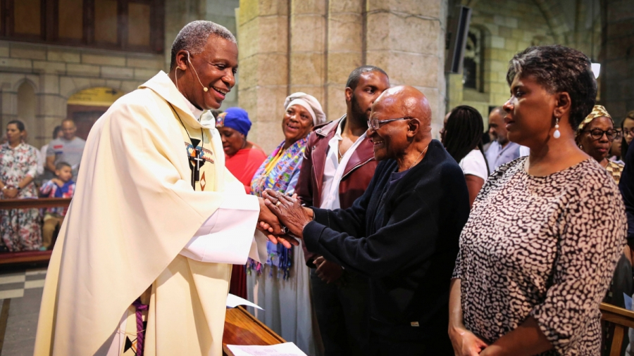 Archbishop Emeritus Desmond Tutu shakes hands with priests inside a church.