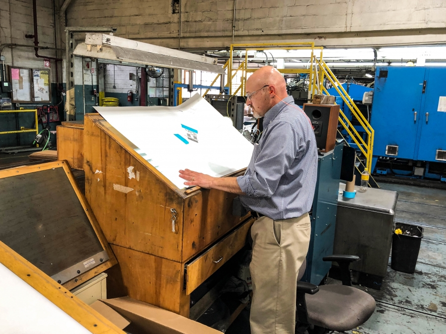 Mohawk paper engineer Paul Graver examines a new batch of paper looking for impurities.