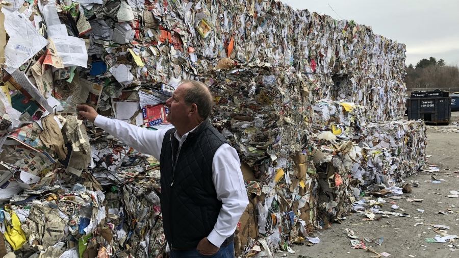 A man in a vest stands next to a wall of baled paper products, about 12 feet tall and several hundred feet long.