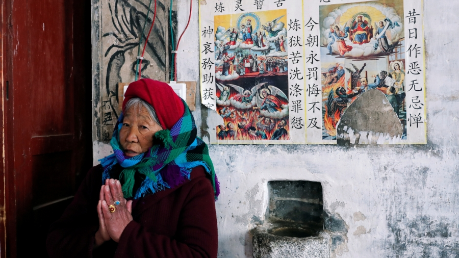 An elderly Tibetan woman prays inside a church in front of religious photos with captions in Mandarin.