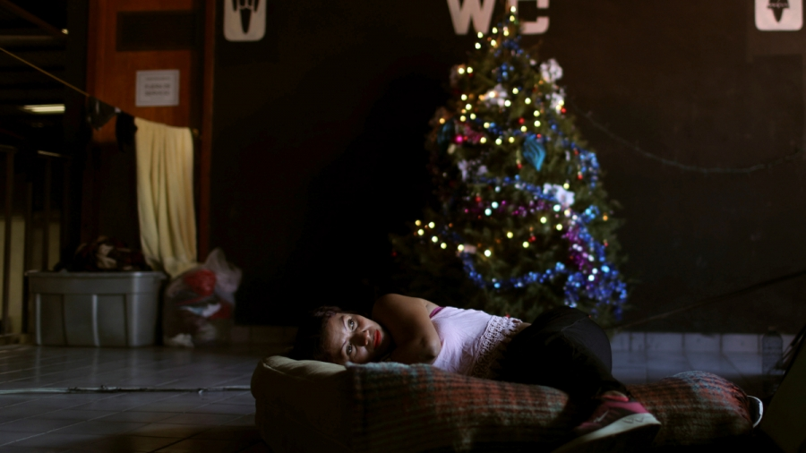 A woman lays on a mattress on the floor in front of a Christmas tree in a dark room in a shelter in Tijuana, Mexico.