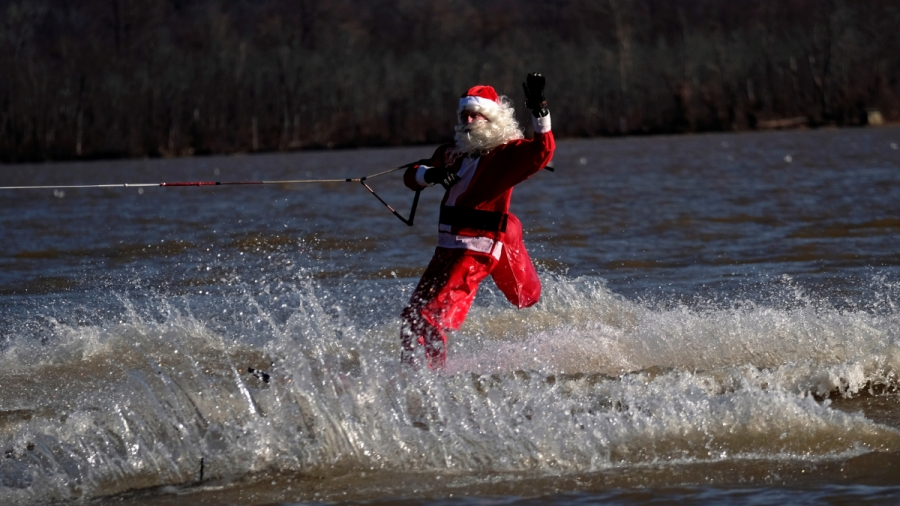 A man dressed up as Santa Claus waterskis on a river.