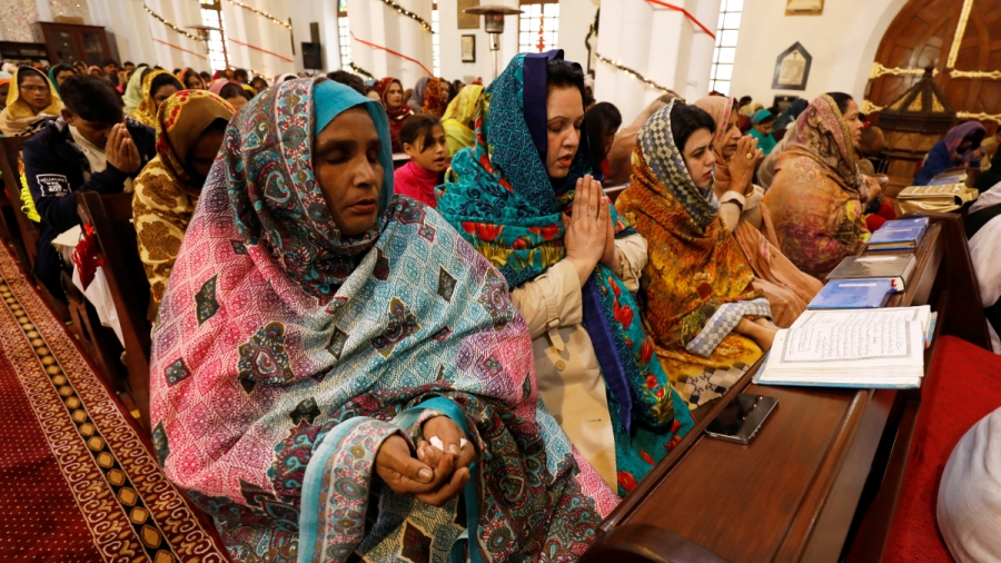 Women in colorful traditional dresses sit down and pray inside a church.