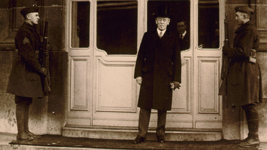 President Woodrow Wilson stands in front of a large window flanked by two soliders