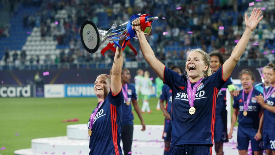 Ada Hegerberg celebrates on a soccer field, holding a trophy and a medal