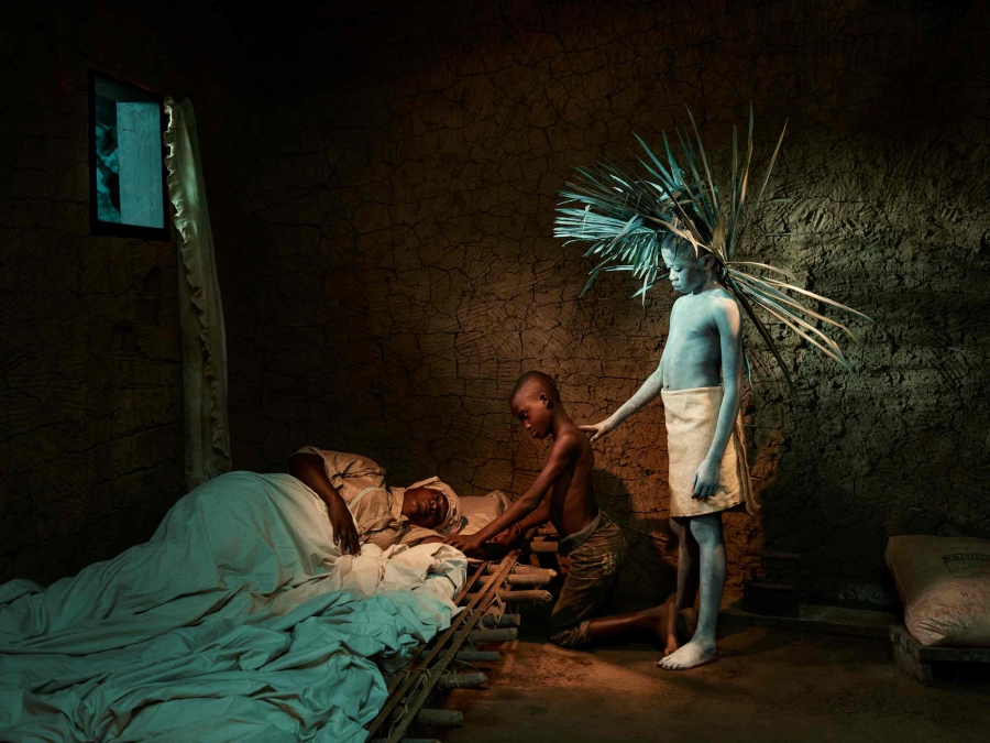 A boy painted white and wearing a headdress of wooden sticks stands over a person lying in bedding on the floor