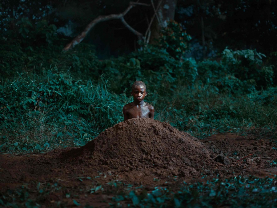 A boy is centered in the frame, inside a small mound, like mole