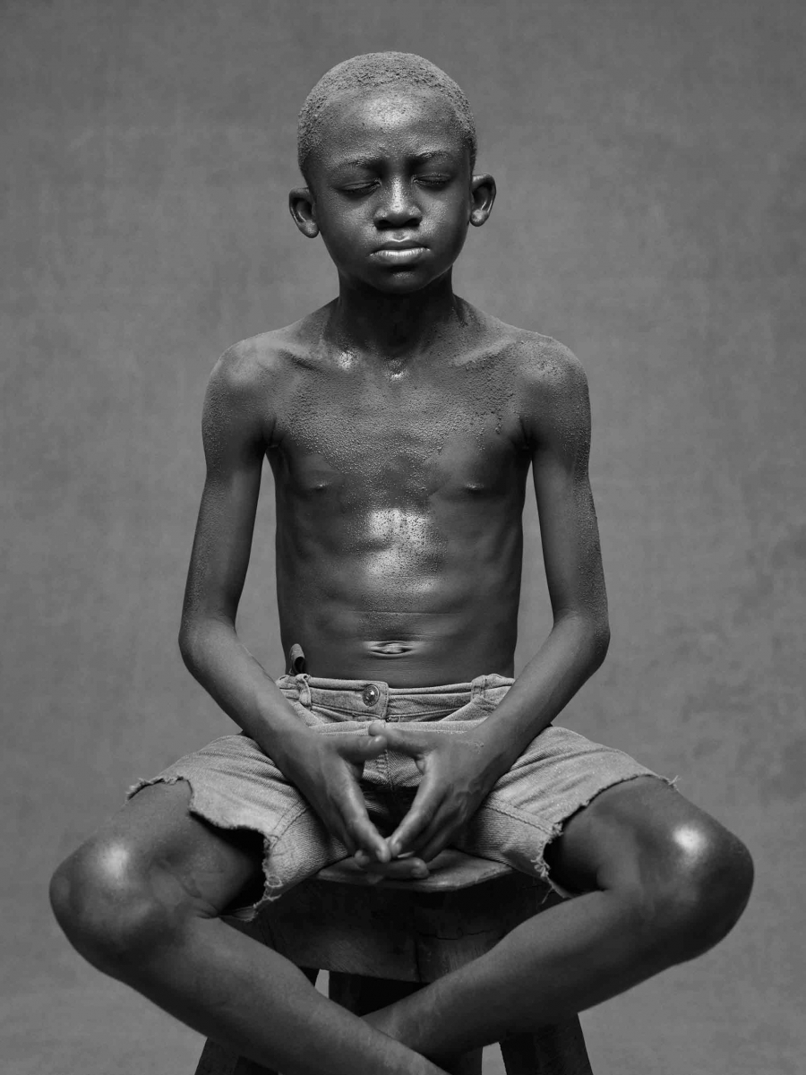 A boy poses for a photograph with his fingers touching and his ankles crossed