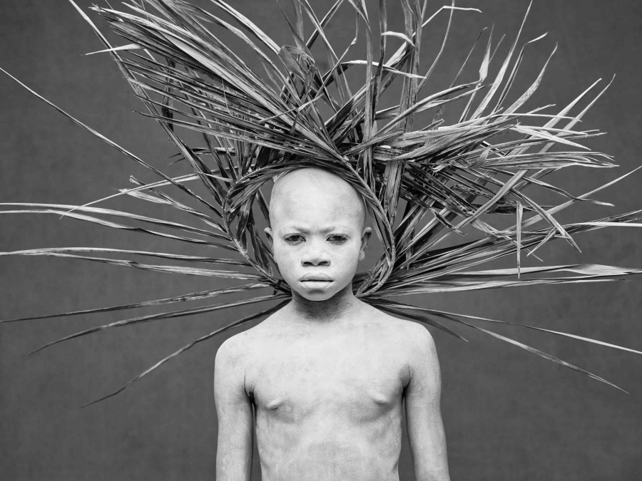 A boy whose body is painted white wears a crown of wooden sticks that looks like a sunburst behind his head poses for a photo