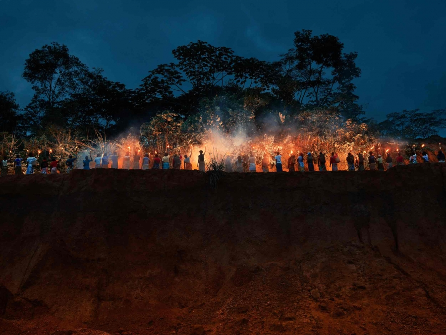 Women stand in a line each holding a torch of fire along a cliff