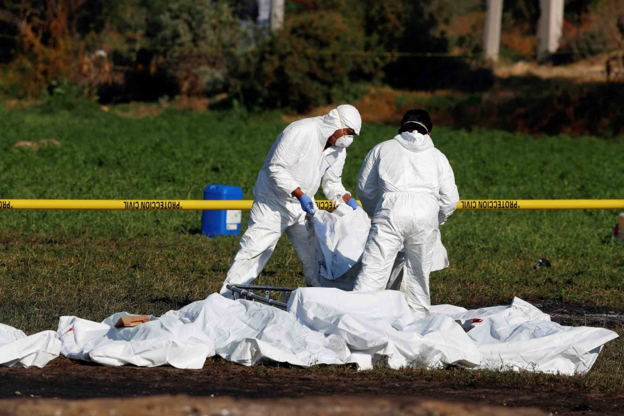 Men in white suits arrange bodies in white bags behind a yellow tape line