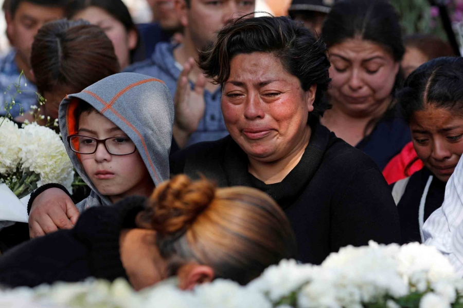 A woman cries and hold onto a young boy as a crowd of people gather for a funeral