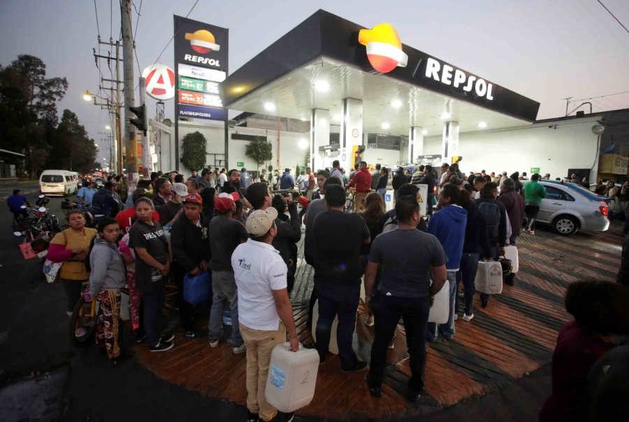 A crowd of people stand in line outside a gas station in Mexico with gas cans in their hands