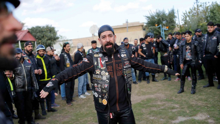 A man wearing all leather is surrounded by about three dozen others wearing similar clothing.