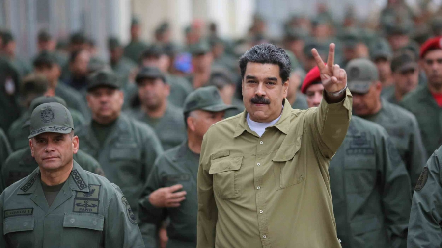 Nicolas Maduro holds up two fingers as he is surrounded by men in military uniforms.
